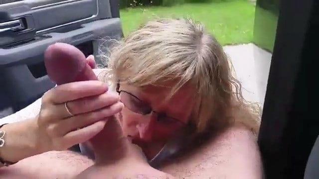 Une cougar suce les couilles et la bite de son voisin à la portière de sa voiture